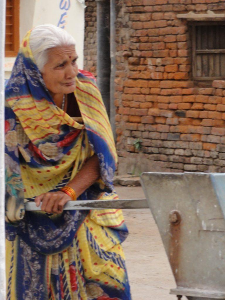 Starsza kobieta pompująca wodę, Udaipur, Indie